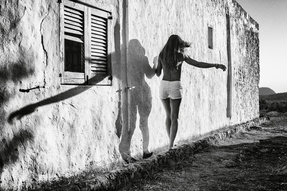 fotografía en blanco y negro de una mujer y una casa de arquitectura tradicional ibicenca al atardecer en ibiza, españa